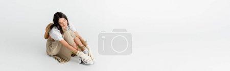 Photo pour Jeune femme souriante en tenue de printemps et gants avec des fleurs assis tout en posant sur blanc, bannière - image libre de droit