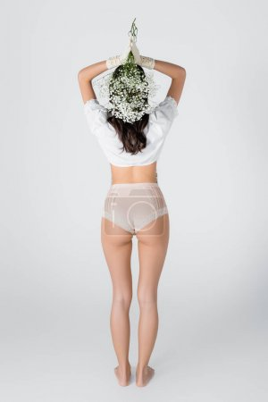 back view of brunette model in gloves and panties with blooming flowers posing on white
