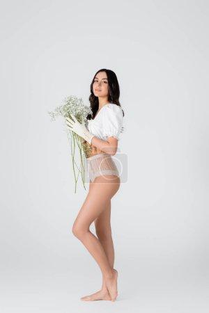 modèle pieds nus pleine longueur en gants et culottes avec des fleurs en fleurs posant sur blanc