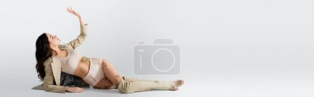 Photo for Brunette model in blazer, crop top and panties with blooming flowers lying while posing on white, banner - Royalty Free Image