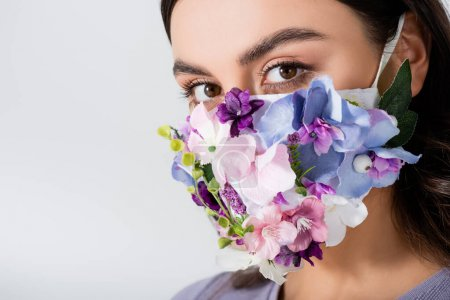 young woman in medical mask with blooming flowers isolated on white