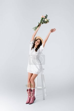 young woman in straw hat and dress holding bouquet of spring flowers above head on white