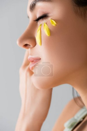 Photo for Close up of young woman with yellow petals on face isolated on white - Royalty Free Image