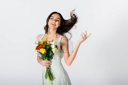 cheerful young woman with petals on face holding bouquet of flowers isolated on white