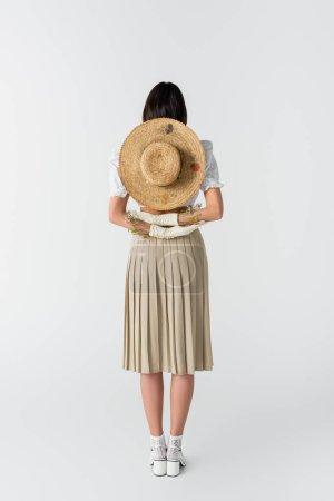 longitud completa de la mujer en guantes con flores y sombrero de paja detrás de la espalda en blanco