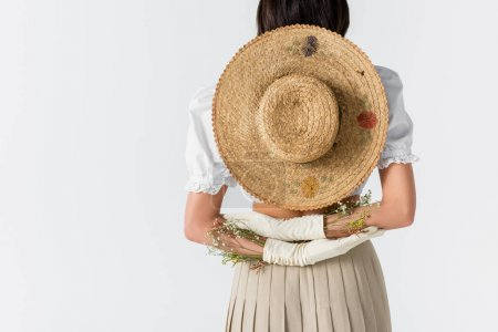 partial view of young woman in gloves with flowers and straw hat behind back isolated on white