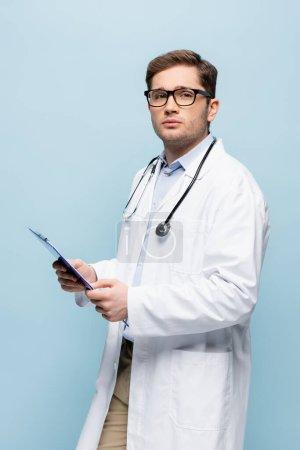 Photo pour Médecin en lunettes et manteau blanc tenant presse-papiers isolé sur bleu - image libre de droit