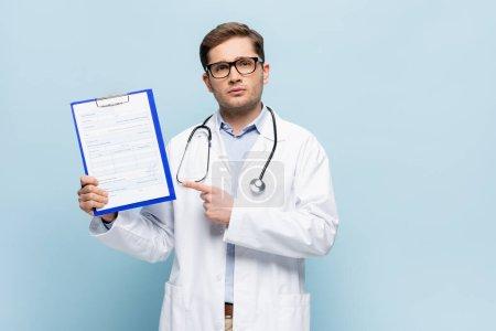 Photo pour Médecin en lunettes et manteau blanc pointant avec le doigt au presse-papiers avec carte médicale lettrage sur bleu - image libre de droit