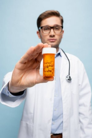 Photo for Bottle with medication in hand of doctor on blurred background isolated on blue - Royalty Free Image