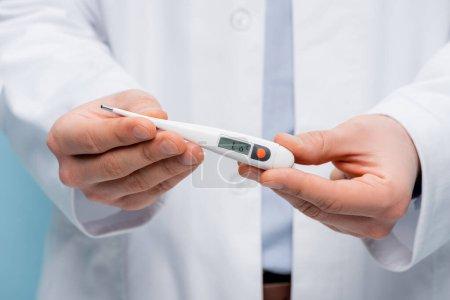 Photo pour Vue partielle du médecin tenant le thermomètre numérique isolé sur bleu - image libre de droit