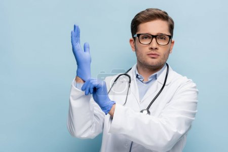 Photo pour Médecin en lunettes et manteau blanc portant des gants en latex sur bleu - image libre de droit