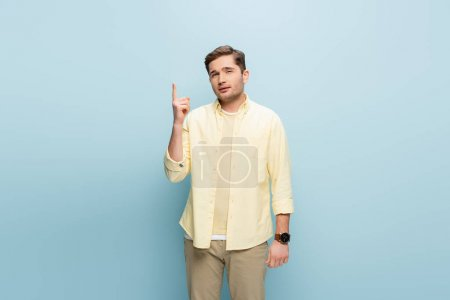 Photo for Young man pointing with finger while having idea isolated on blue - Royalty Free Image