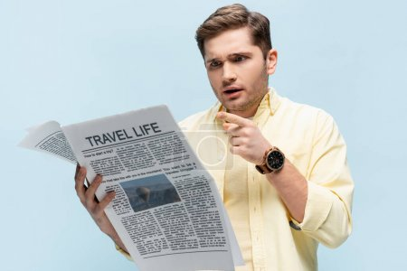 Photo pour Jeune homme en chemise pointant du doigt le journal de voyage isolé sur bleu - image libre de droit