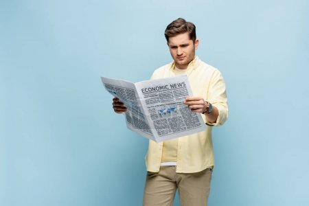 displeased young man in shirt reading economical newspaper on blue