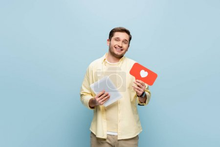 happy man in shirt holding paper heart and digital tablet isolated on blue