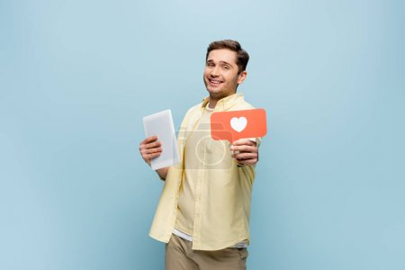 cheerful man in shirt holding paper heart and digital tablet isolated on blue