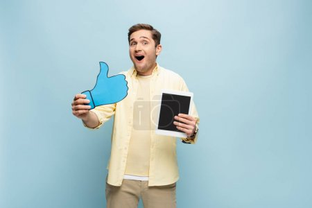 Photo pour Homme étonné en chemise tenant du papier comme et tablette numérique avec écran blanc isolé sur bleu - image libre de droit