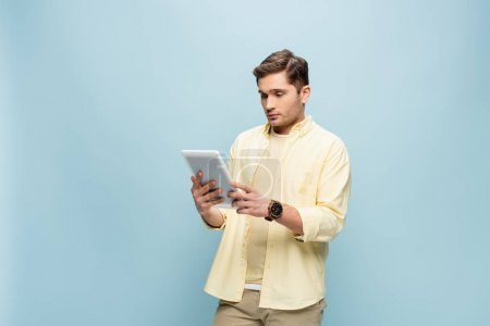 young man in yellow shirt looking at digital tablet isolated on blue