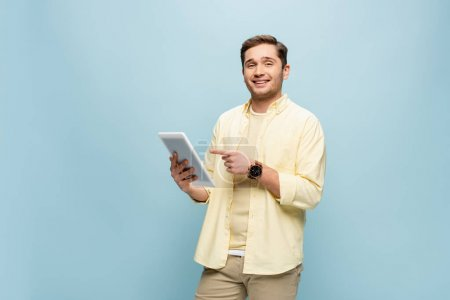 cheerful man in yellow shirt pointing with finger at digital tablet isolated on blue