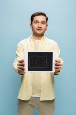smiling young man in yellow shirt holding digital tablet with blank screen isolated on blue