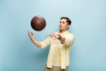 man in yellow shirt throwing basketball in air on blue