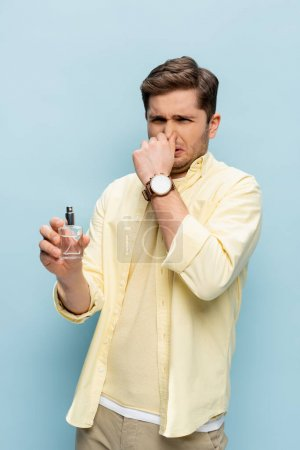 disgusted young man in yellow shirt holding bottle with perfume and covering nose on blue