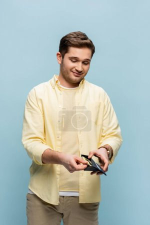 happy young man in yellow shirt holding wallet with dollars isolated on blue