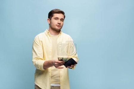 Photo pour Jeune homme en chemise jaune tenant portefeuille avec des dollars isolés sur bleu - image libre de droit