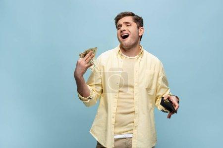 Reicher junger Mann in gelbem Hemd mit Brieftasche und winkenden Dollars