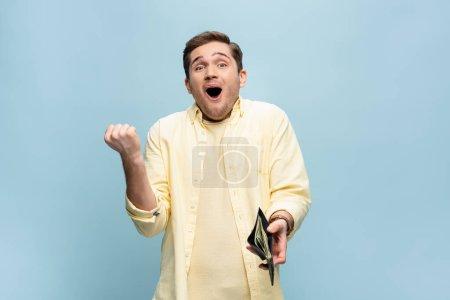 Photo pour Excité jeune homme en chemise jaune tenant portefeuille avec des dollars isolés sur bleu - image libre de droit