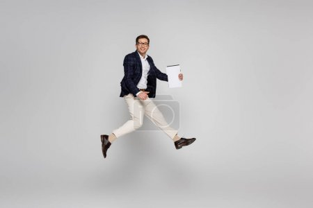 longitud completa de alegre hombre de negocios en gafas sosteniendo papel mientras salta sobre gris