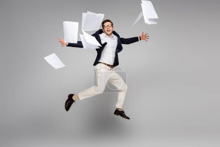 full length of excited businessman jumping near documents in air on grey