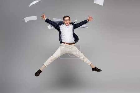 Photo for Full length of cheerful businessman jumping near papers in air on grey - Royalty Free Image