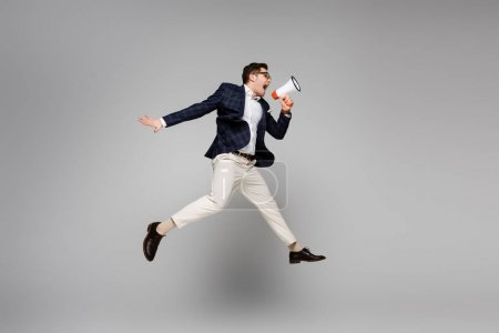 Photo for Full length of businessman jumping and screaming in megaphone on grey - Royalty Free Image