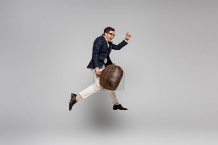 full length of amazed businessman holding leather bag and levitating on grey