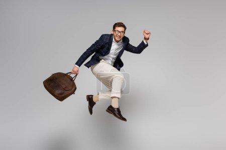 pełna długość radosnego biznesmena trzymającego skórzaną torbę i lewitującego na szarym