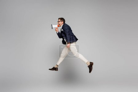 Photo for Side view of businessman jumping and screaming in megaphone on grey - Royalty Free Image