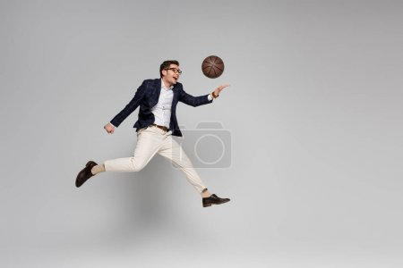 full length of cheerful businessman playing basketball while levitating on grey