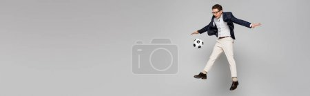 Photo pour Pleine longueur de joyeux homme d'affaires jouant au football tout en lévitant sur gris, bannière - image libre de droit