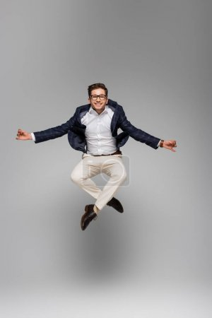 full length of cheerful businessman in glasses meditating and levitating on grey