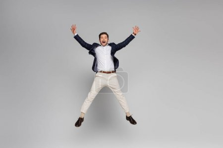 full length of excited man with outstretched hands levitating on grey