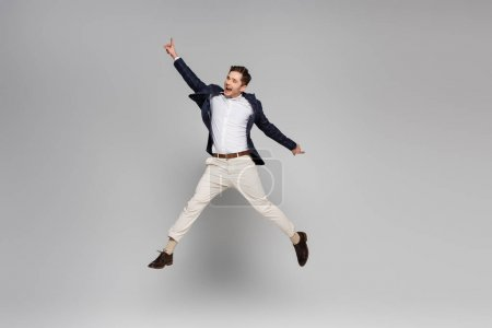 full length of excited young man with outstretched hands levitating on grey