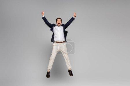 volle Länge des aufgeregten Mannes mit ausgestreckten Händen, die auf grau springen