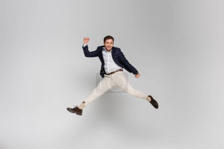 full length of happy young man with clenched fists levitating on grey