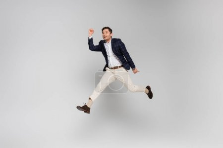 full length of cheerful young man with clenched fists levitating on grey