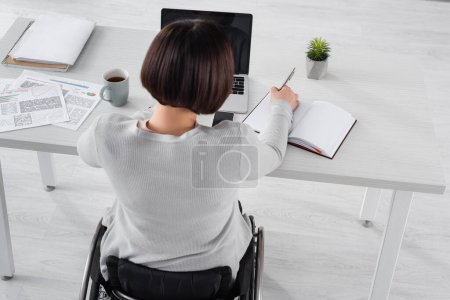 Photo for Overhead view of freelancer in wheelchair writing on notebook near laptop and papers - Royalty Free Image