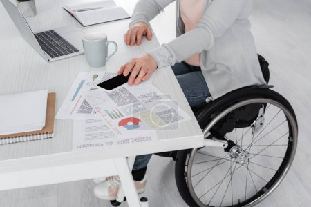 Photo for Cropped view of disabled freelancer taking smartphone near laptop and documents on table - Royalty Free Image