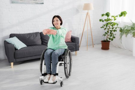 Positive woman in wheelchair stretching during training at home