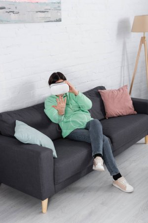 Woman in vr headset playing video game on sofa in living room