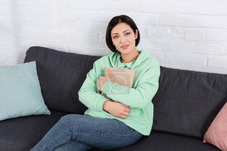 Lächelnde Frau mit Buch blickt auf der heimischen Couch in die Kamera